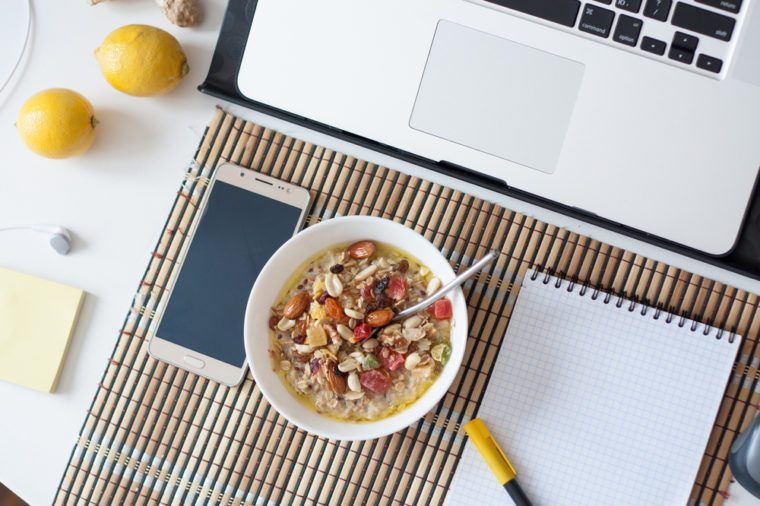 Healthy breakfast in front of computer laptop. oat porridge with smart phone notebook lemons note sticks on office table. Freelancers or programmer's workspace. Cozy workplace in tropical interior.