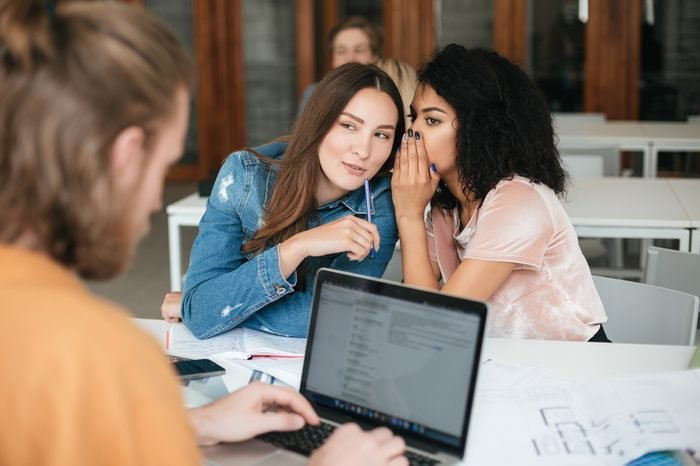 Portrait of two smiling beautiful girls sitting in classroom and gossiping while young man working on his laptop. Pretty girl with dark curly hair saying secret to her friend in office