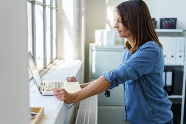 Businesswoman standing at a large window sill using her laptop computer in the bright daylight in a profile view