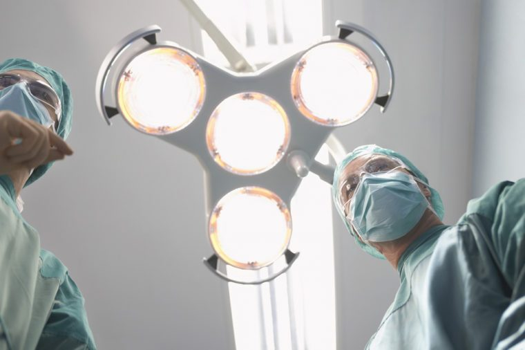 Low angle view of two surgeons under surgery lights in operating theatre