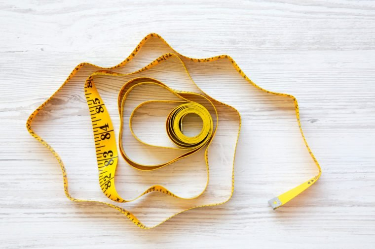 Yellow measuring tape on white wooden background, from above. Top view.