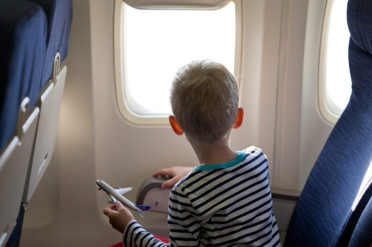 little boy in the plane looking out the window