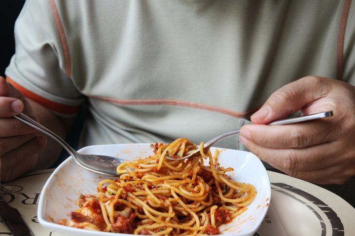 Fresh spaghetti with tomato sauce and man hand, Low angle view of a serving of Italian spaghetti with a meat based bolognese,
