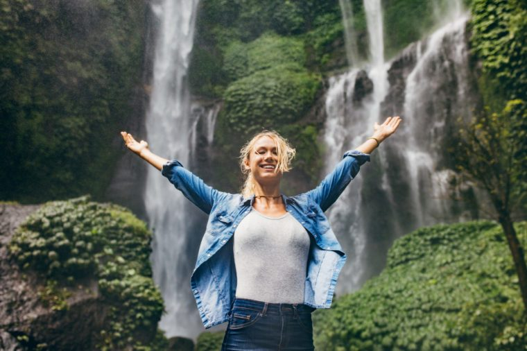 Happy young woman spreading hands enjoying nature with waterfall in background. Caucasian female standing in front of a waterfall with her arms outstretched.
