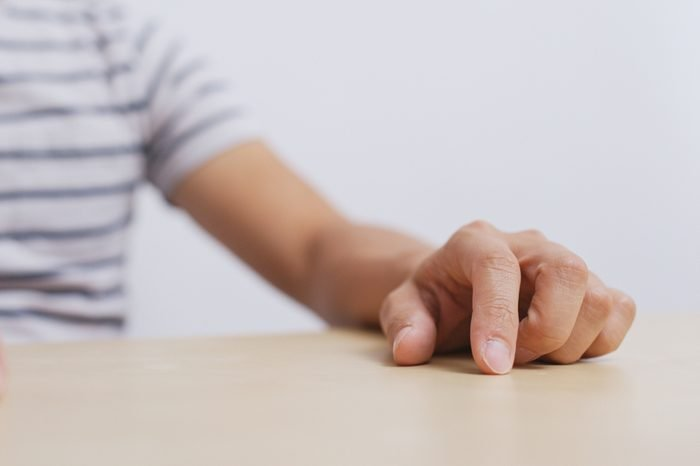 Adult man hand finger tapping on table