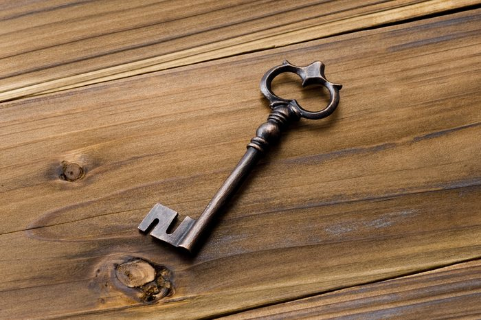 Old key on wooden table.