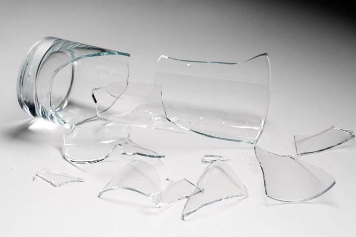 broken glass against grey background, concept of danger