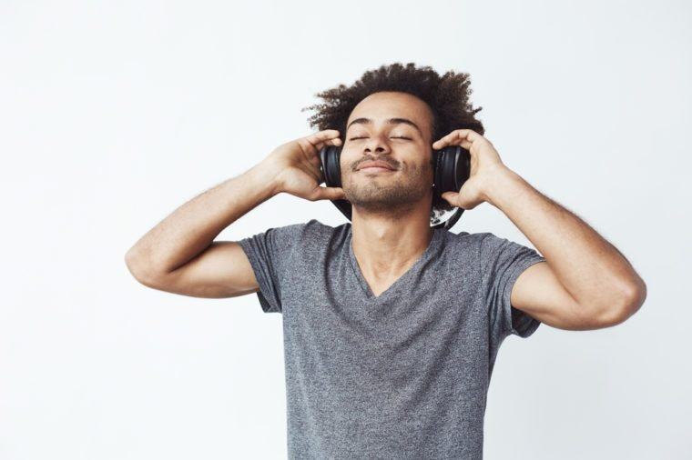 Happy african man smiling listening to music in headphones. Closed eyes.