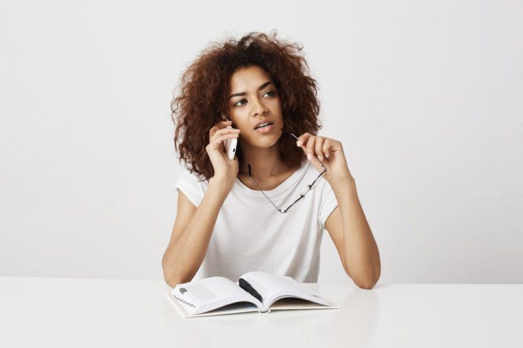 African girl talking on phone thinking sitting at table over white background. Copy space.