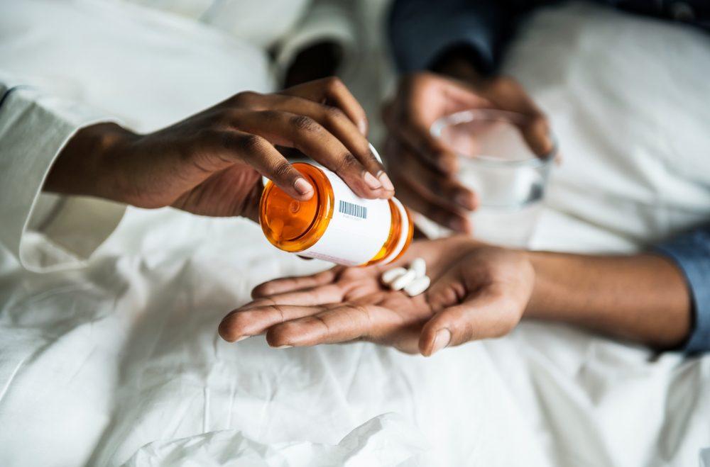 A woman handing pills to her boyfriend