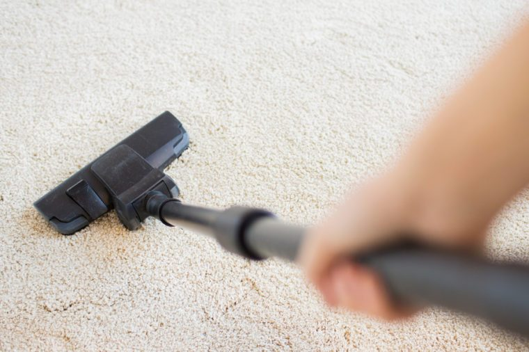 people, housework and housekeeping concept - close up of hand with vacuum cleaner cleaning carpet at home