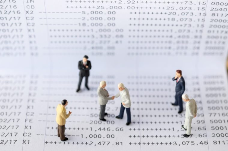 Business Concept. Two tiny miniature figures of businessman standing on a bank book document with a handshake and group of businessman miniature figure standing around for a meeting.