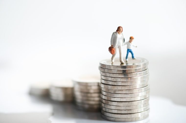 Miniature people: Woman and child standing on rows of stack coins using as background Money, Financial, Business Growth and family concept,