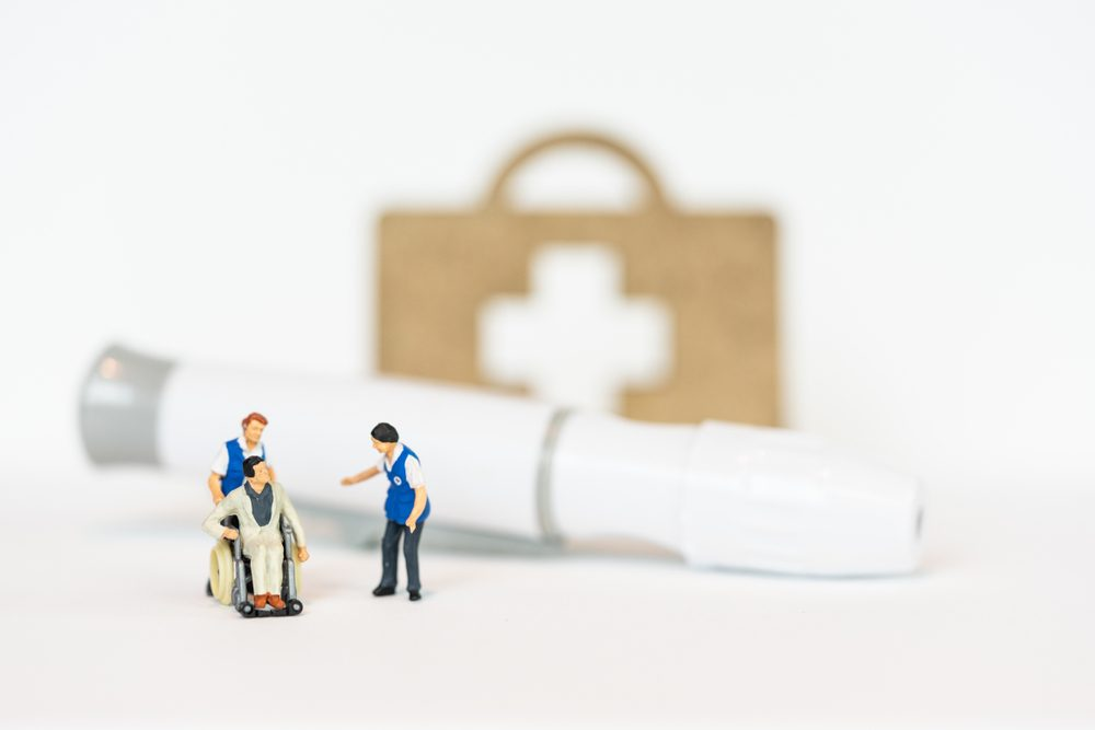 Miniature people, patient in wheel chair and blood glucose meter, lancet.Healthcare medical and check up, diabetes, glycemia, and people concept.