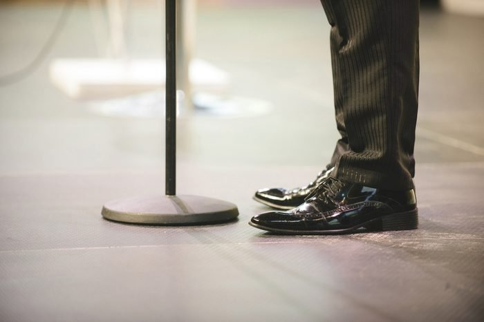 male feet in black shoes at microphone stand at hall