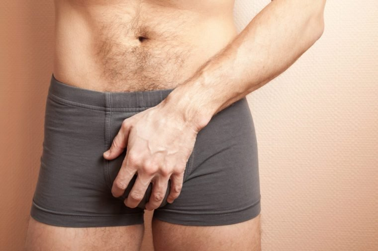 Young adult sporty man holding his genitals with hand in boxer underpants, close up studio photo with selective focus