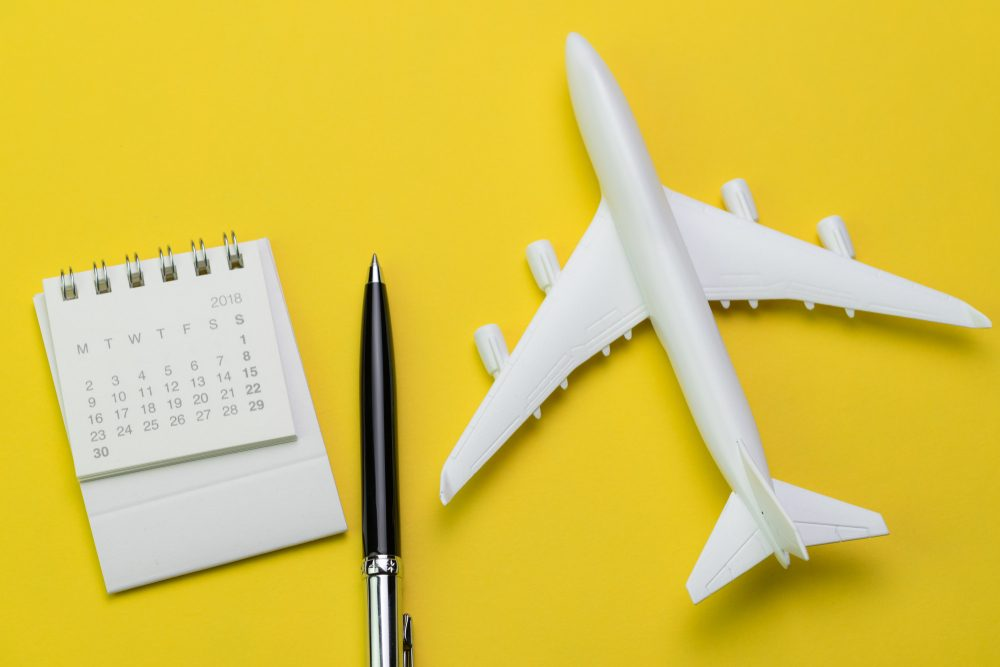Flat lay of travel and tourism concept, small white clean paper calendar with black pen and toy airplane on vibrant yellow background.