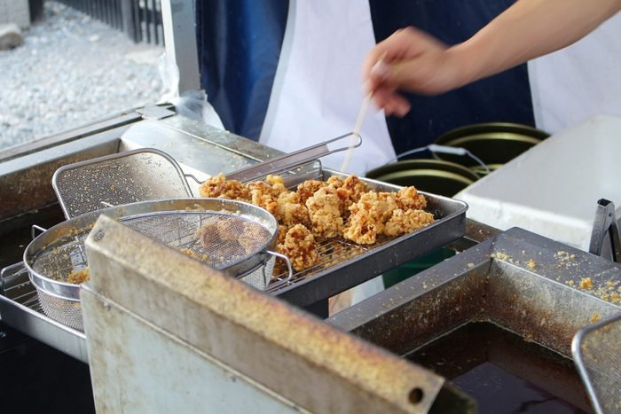 Japanese fried chicken is cooked and rest for oil drain side of pot and other cooking equipment in restaurant or food kiosk. Food for picnic in holidays. Old and reuse oil. Dirty oil. Temple market