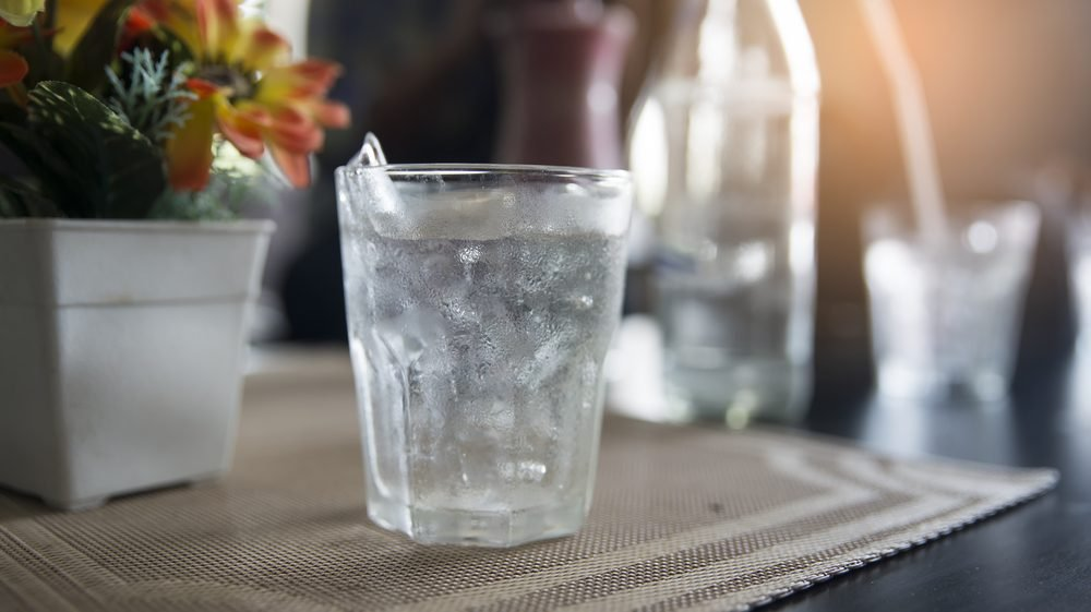 Glass of drinking ice water with ice cube placed on glass table with bokeh background.Ice Water Drinking Concept.