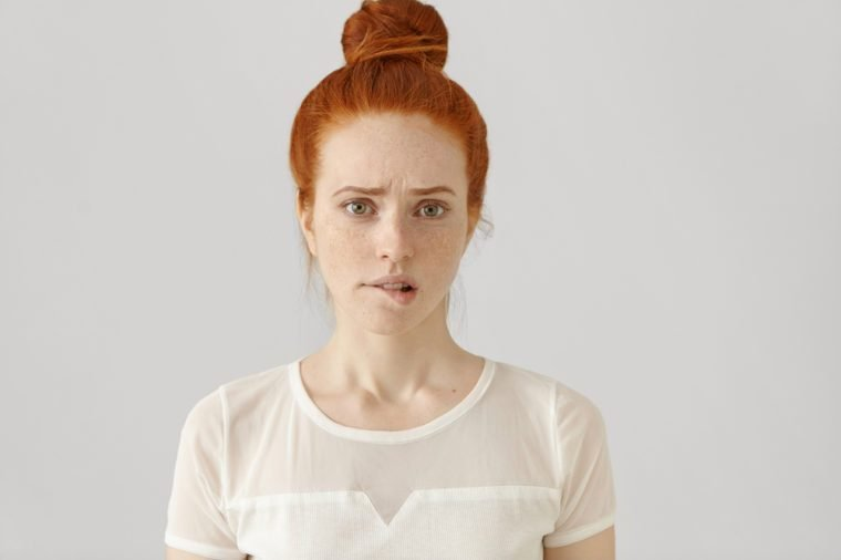 Confused or puzzled beautiful young Caucasian woman with ginger hair frowning, biting her lower lip after having done something wrong, looking at camera with guilty and apologetic facial expression