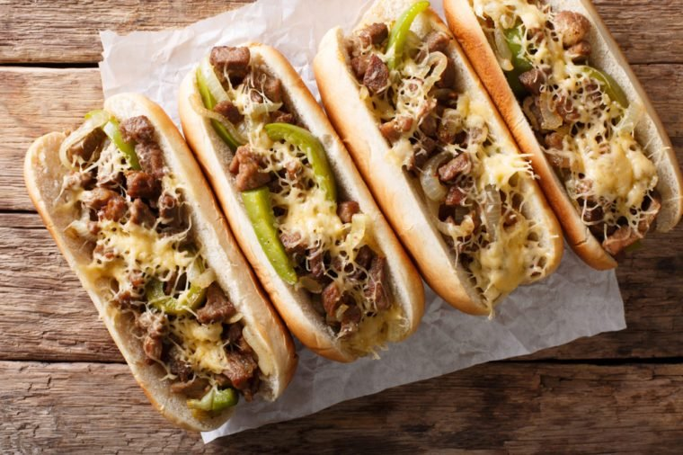 Philly cheese steak sandwich served on parchment paper close-up on the table. Horizontal top view from above