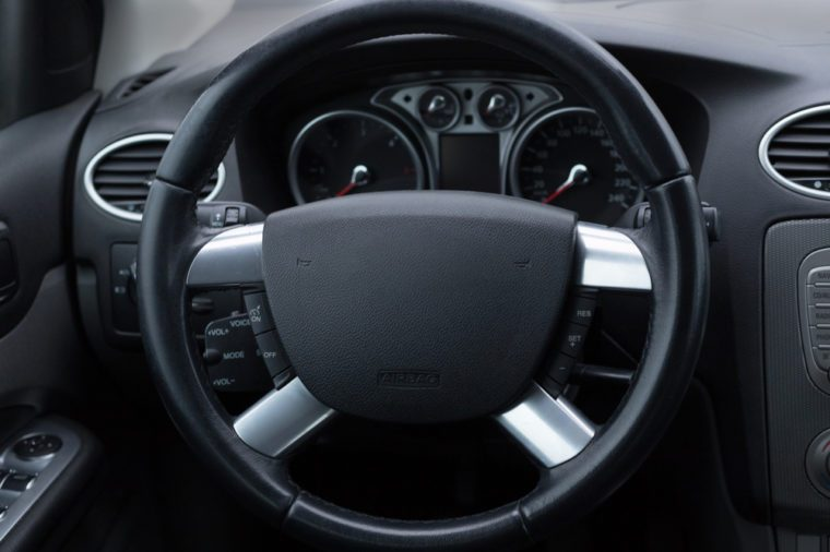 Interior of the vehicle speedometer panel and steering wheel with focus on some parts
