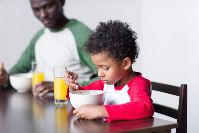 happy african-american father and little son eating breakfast