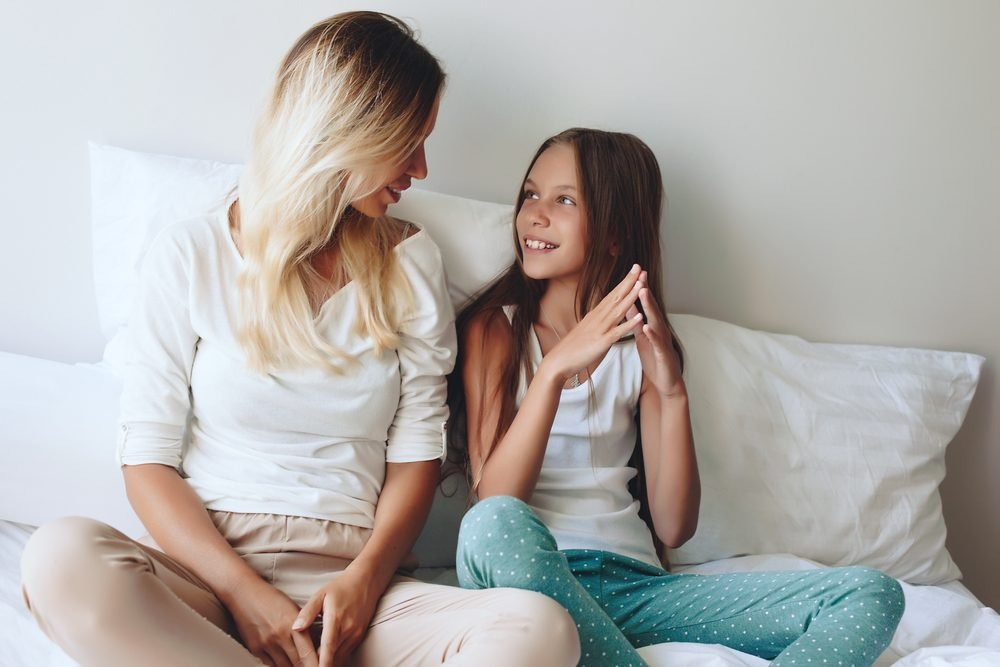 Mom with her tween daughter relaxing in bed, positive feelings, good relations.