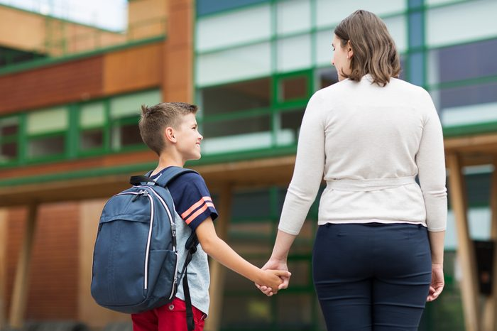 education, childhood, family and people concept - elementary student boy with mother at school yard