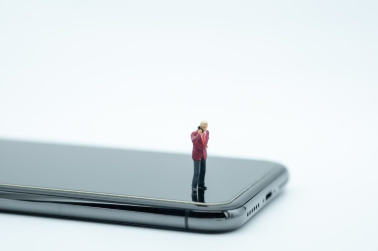 Communication and business concept. Businessman miniature figure standing and talking mobile phone on smart phone on white background.