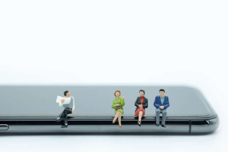 Technology and communication concept. Group of man and woman miniature people figures sitting and talking on smart phone on white background.