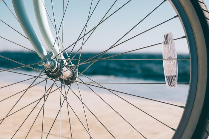 Bicycle wheel with reflector close-up on the blurred background of the sea beach at sunny summer day.