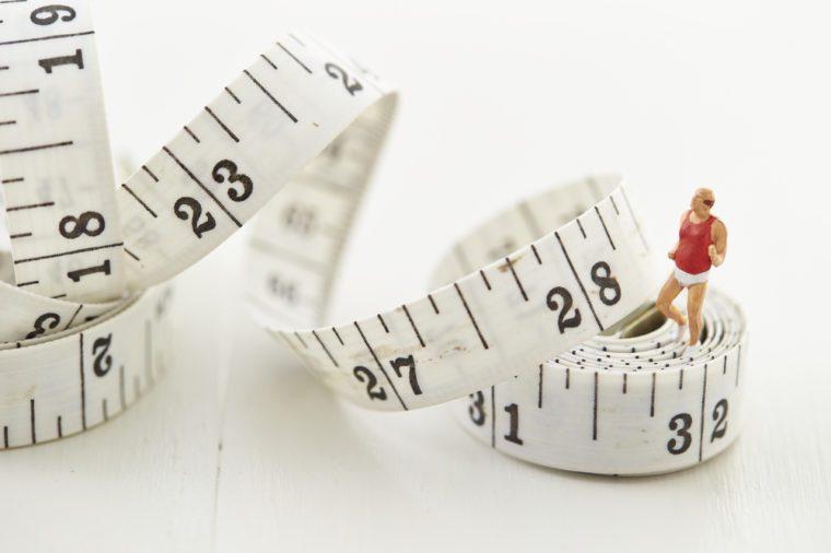 Miniature woman on tape measure