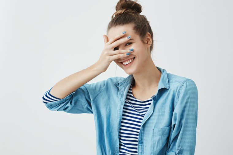 Girl saying silly words and gets embarrassed. Indoor shot of cute slender woman in stylish garment, covering eyes with hand but peeking, smiling broadly at camera, expressing positive emotions
