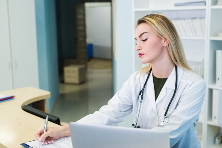 Smiling nurse with laptop scheduling appointment for male patient at reception