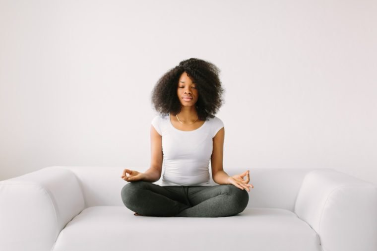 An African American young women sitting in the lotus position on white bed.