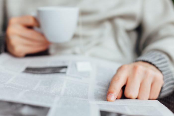 Closeup of man reading newspapers