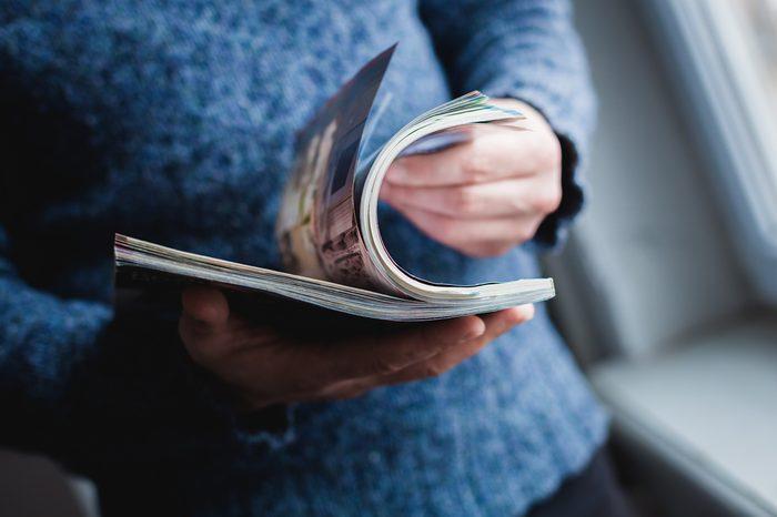 A man looks at a magazine. Press hands.