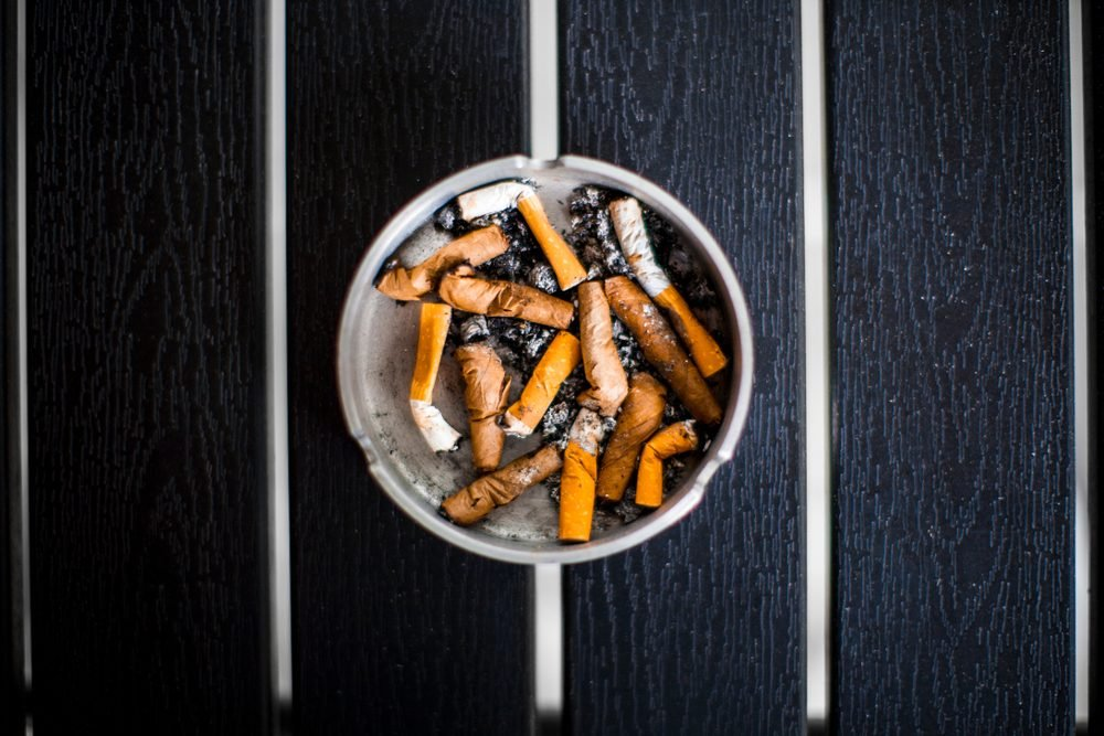 An ashtray with old smoked cigarettes stands on a black table top view, day