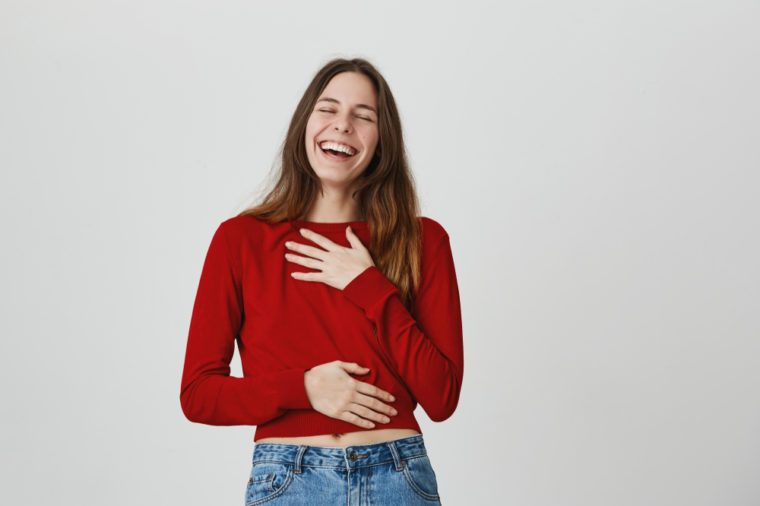 Good-looking attractive female with long dark hair and closed eyes dressed in red sweater and jeans laughing at someone`s joke during conversation. Young woman expressing positive emotions
