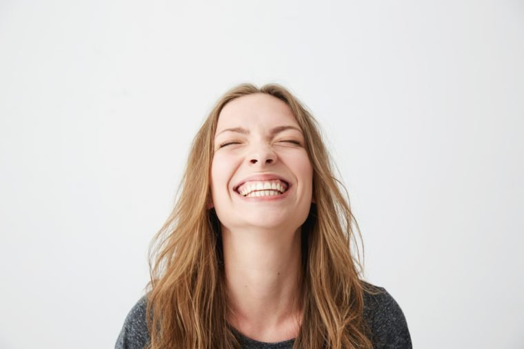 Portrait of young emotional beautiful girl laughing with closed eyes over white background.
