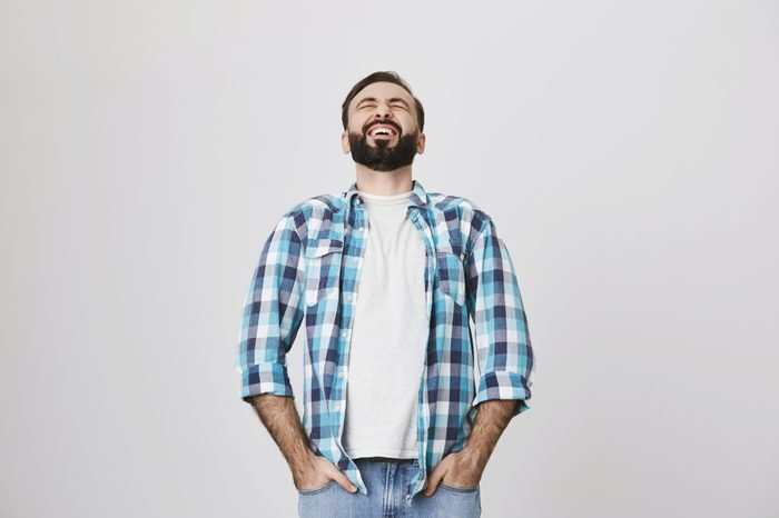 Studio shot of handsome european adult with beard and moustache, laughing out loud, stooped back, holding hands in pockets of jeans, over gray background. Guy watches stand up show on TV