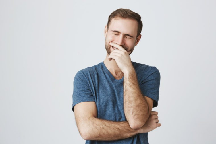 Funny smiling unshaven male wears casual blue clothes, being glad, expresses positive emotions, laughs at joke with closed eyes. People, happiness, positiveness concept
