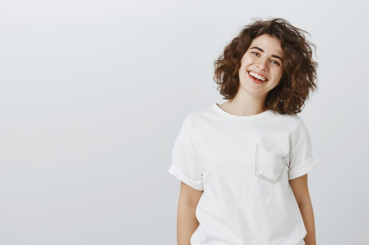 Inviting us come and dinner together. Portrait of positive friendly-looking attractive girlfriend in white t-shirt, smiling broadly and expressing good attitude while talking casually with coworkers