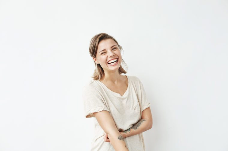 Cheerful happy young beautiful girl looking at camera smiling laughing over white background.