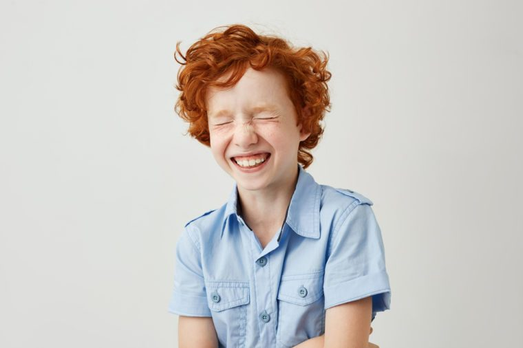 Close up portrait of cheerful little kid with curly ginger hair and freckles laughing with closed eyes after hearing funny joke from friend.