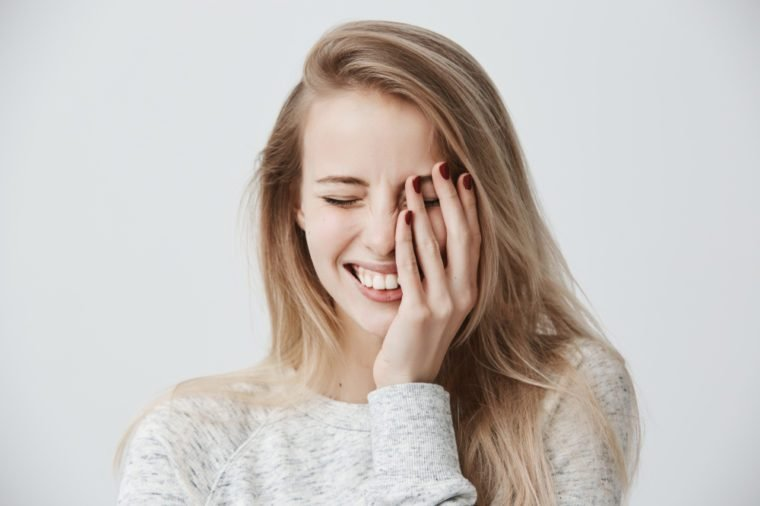 Positive emotions concept. Beautiful happy Caucasian blonde woman dressed casually smiling broadly, showing her perfect white teeth, relaxing, closing eyes because of joy, spending weekend indoors