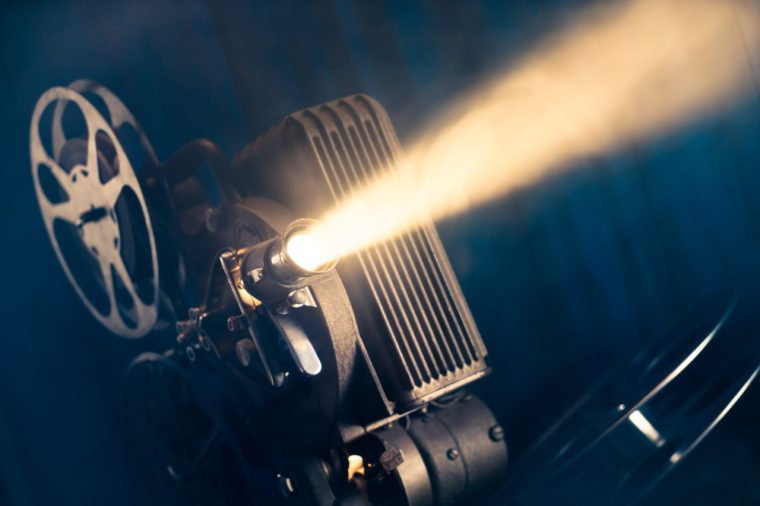 film projector on a wooden background with dramatic lighting and selective focus