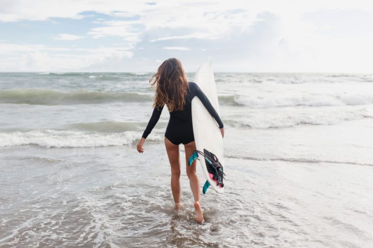 Young sporty active woman dressed swimsuit runs in the ocean with surf board in sunny day. Surfer girl walking with board on the sandy beach.