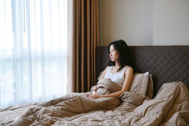 sad depressed woman thinking on bed in luxury bedroom